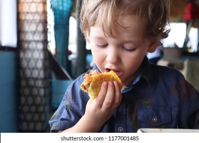 Little Kid eating taco on a restaurant in the beach, Okinawa Japan