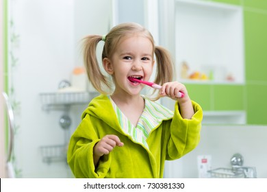 Little kid girl brushing teeth in bathroom