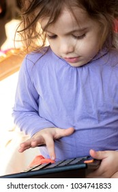 Little kid girl with a calculator in hands.