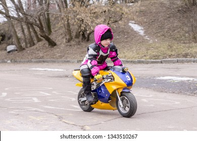 little kid girl child female gender on a sports moto bike rides along the street in early spring in late winter A child in a helmet and sports protective clothing on a minimoto motorcycle baby driving
