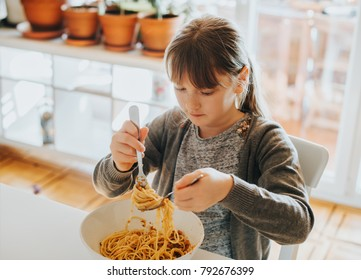 Little kid girl eating spaghetti bolognese at home for lunch
