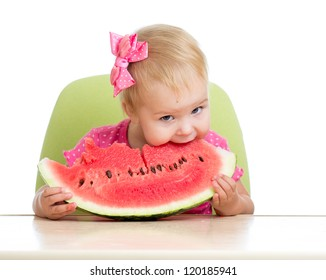 Little kid girl eating watermelon at table isolated on white background