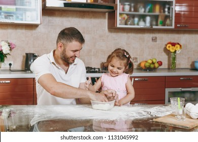 Little kid girl helps man to cook Christmas ginger cookies in kitchen at table. Happy family dad, child daughter cooking food in weekend morning at home. Father's day holiday. Parenthood, childhood