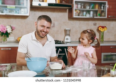 Little kid girl helps man to cook Christmas ginger cookies, plays with flour at table. Happy family dad, child daughter cooking food in weekend morning. Father's day holiday. Parenthood, childhood