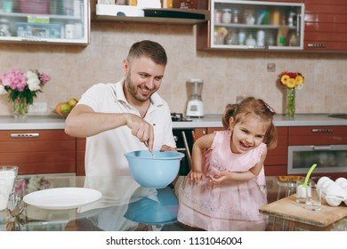 Little kid girl helps man to cook Christmas ginger cookies, stirs dough in bowl at table. Happy family dad, child daughter cooking food in weekend morning. Father's day holiday. Parenthood childhood