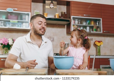 Little kid girl helps man to cook Christmas ginger cookies, stirs eggs, dough in bowl at table. Happy family dad, child daughter cooking food in weekend. Father's day holiday. Parenthood, childhood