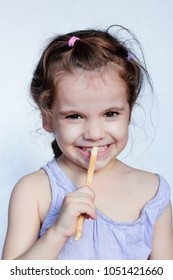 Little kid girl holding miswak in hands and making teeth cleaning procedure.