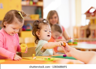 Little kid girl learning to use colorful play dough in kindergarten. Babies group studying in primary school