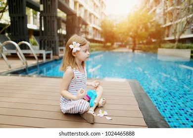 little kid girl in lotus position doing yoga exercises sitting close to blue swimming pool wearing flower. concept of thealthy habits, kids education or enjoying life on sunny day