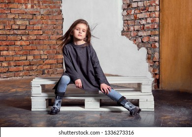 Little kid girl model posing fashionable in casual stylish clothes, gumboots. Fashion child sitting pose. studio background, brick wall.Shop youth, advertisement.