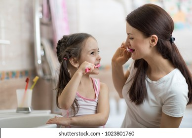 Little kid girl and mom brushing teeth in bathroom
