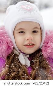 Little kid girl on snowy winter day outdoor.