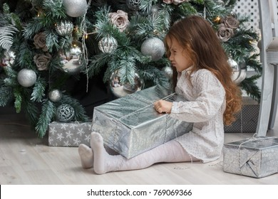 Little kid girl sitting near the christmas tree with the gift at hand.