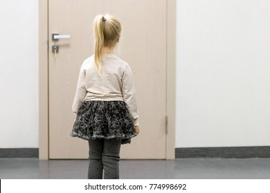 Little kid girl standing  in front of doctors door and afraid to enter.  Concept of kids phobia or fear .