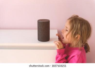 Kleines Kind, das mit Amazon Alexa Echo Dot spricht. Bildungsprogramm für Kinder. Junge Mädchen spricht mit Alexa und gibt es Befehle und Befehle, was zu schalten.