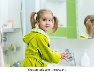 Little kid girl washing her hands in the bathroom