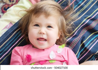 little kid happy smiling lying on bed, happy childhood concept