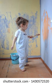 Little kid having fun with paint brush, helping renovating walls by color paints