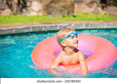Little Kid Having Fun in Swimming Pool, with Goggles and Raft. Summer Vacation Fun.