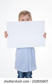 little kid hides her face behind rectangular leaf