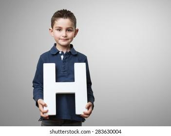 little kid holding the h letter