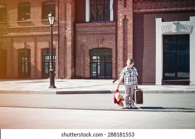 little kid is holding the suitcase and teddy bear toy crossing the sunny street in the morning