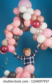 Little kid holds ballon arch above his head on blue background. Background. Child and arch. Happy emotions from cheerful kid with ballons. Simple decorations children's celebrations