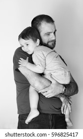 little kid hugging to his father very strong in black and white