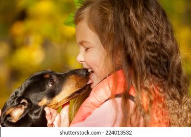 Little kid kissing dachshund puppy. Love to animals concept