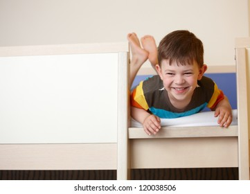 Little kid laughing on top of bunk bed, laying on front.