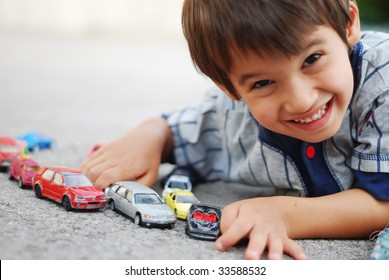 A little kid is laying and playing with cars