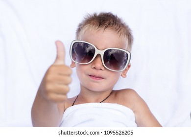 A little kid lies on a white blanket in white glasses and is happy