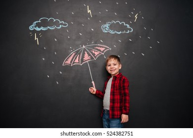 Little kid looking at camera while holding umbrella on the chalkboard with drawings of a rain.