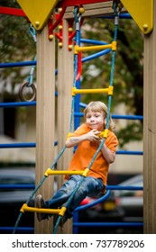 Little kid in an orange t-shirt climbing a rope ladder on a playground