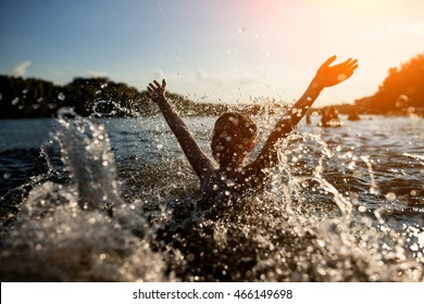 little kid play in water and making splash; child swim in lake or river and have fun with drops;