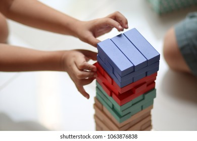 little kid play wooden block at the top