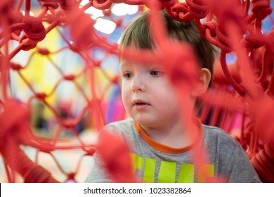 Little kid playing behind the net at indoor playground