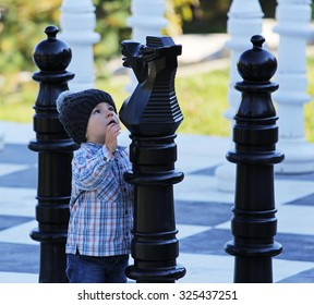 Little kid playing big chess