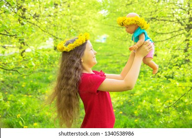 Little kid is playing with a doll. Adorable little girl with long hair lifts a baby doll up. The child and the doll are dressed in wreaths of dandelion flowers. Summer holidays