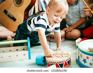 Little kid playing with a wooden drum set