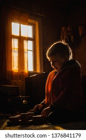 Little kid playing with wooden toys bricks indoors backlit golden morning light sun rays. Boy child constructing castles at country house home alone. Free happy childhood natural games boredom