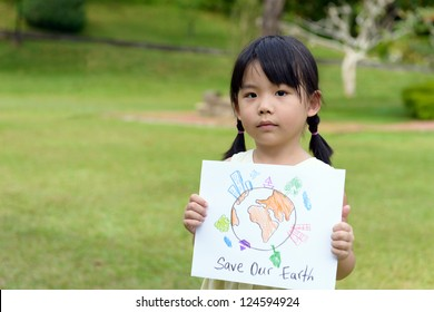 Little kid showing save our earth drawing in a park
