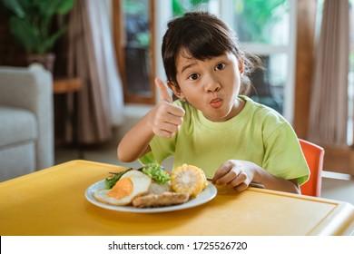 家で朝食を食べながら親指を出す小さな子ども