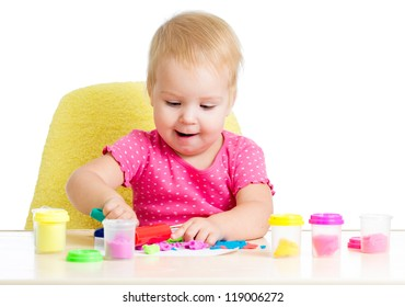 Little kid sitting at table playing with colorful clay