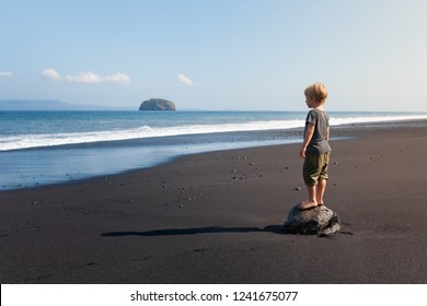 Little kid stand on big stone on black sand sea beach. Dreaming child look at sea surf, waves. Solitude concept. Retreat leisure on summer family vacation