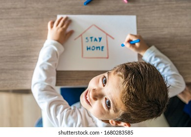 Little kid with Stay Home draw. Coronavirus concept