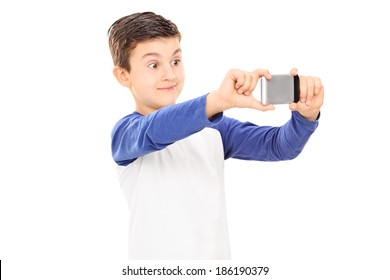 Little kid taking a selfie with cell phone isolated on white background