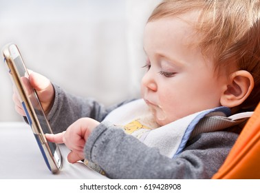 little kid try to use modern smartphone during dinner