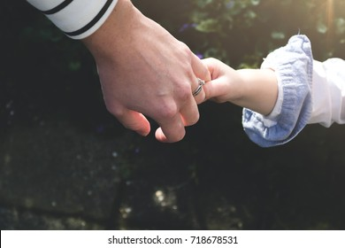 Little kid wants to show his mother something. Holding hands of his mom trying to get her to come with him. Close up.