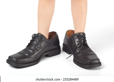 Little kid wearing adult's shoes that are too big